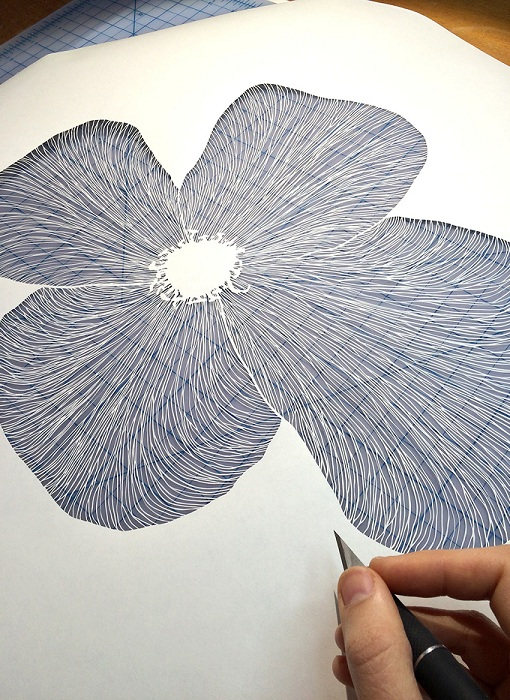 Процесс вырезания цветка из бумаги.