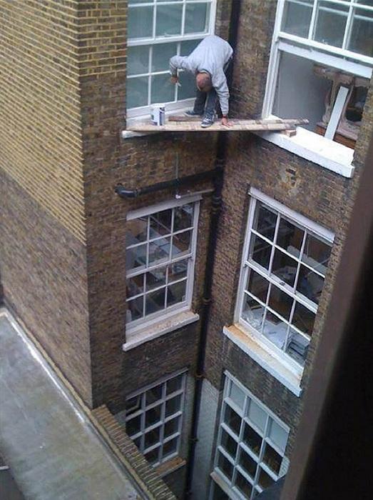 Мужчина красит окно, стоя лишь на двух жердочках.