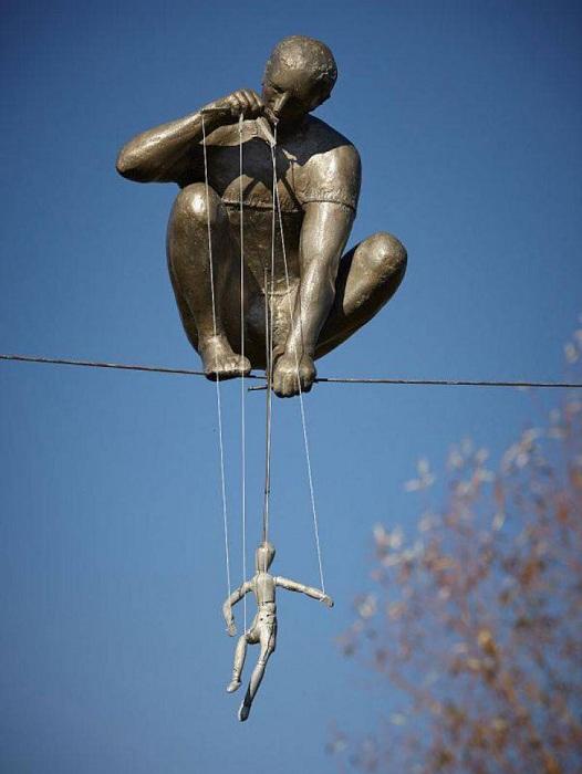 Кукольник с марионеткой, сидящий на канате. Сад скульптур Энн Нортон в Уэст-Палм-Бич штата Флорида.