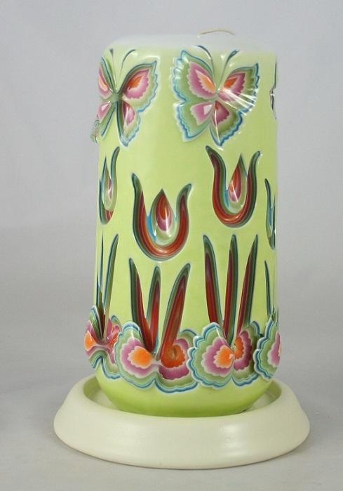 Яркая, цветная свечка с вырезанными узорами.