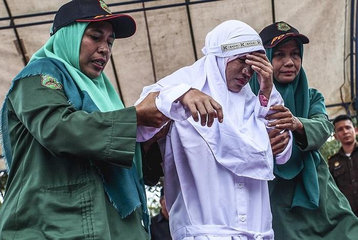 После исполнения наказания женщину выводят полицейские. | Фото: dailymail.co.uk.
