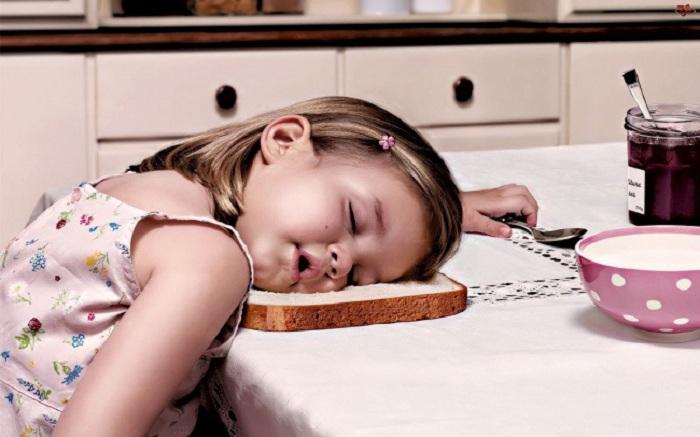 Девочка уснула прямо на кусочке хлеба.