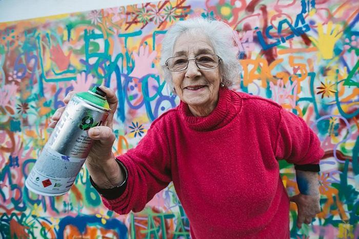 Пожилые люди рисуют граффити на городских стенах.