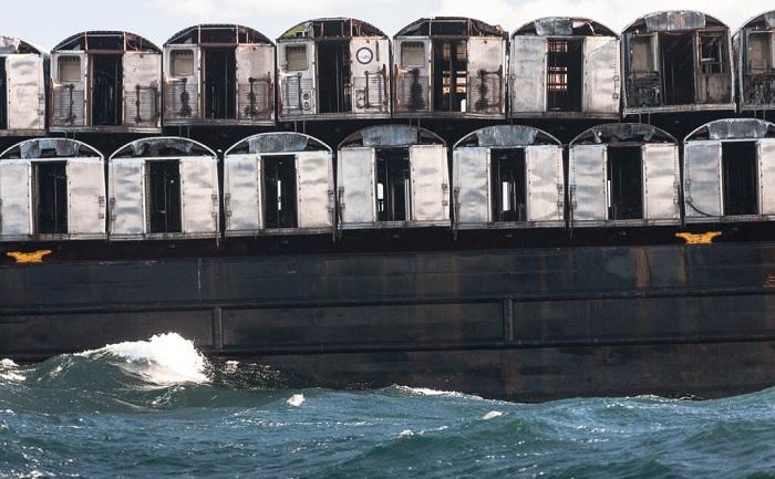 Сотни вагонов сбрасываются в океан.