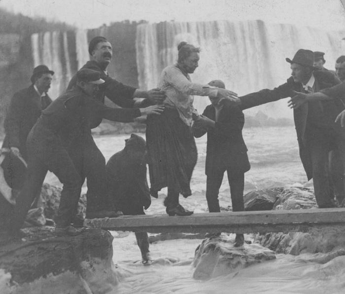 Мужчины, помогающие Энни Эдсон Тейлор выбраться после падения с Ниагарского водопада. | Фото: mashable.com.