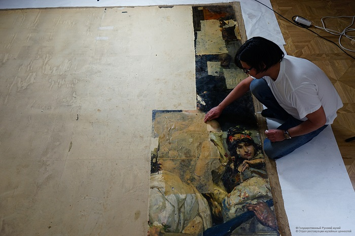 Процесс снятия бумажной заклейки. | Фото: restoration.rusmuseum.ru.