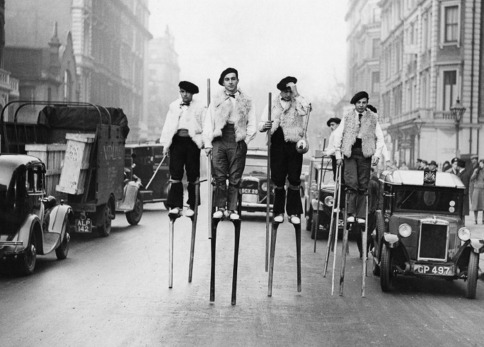Танцоры на ходулях (из ланд), прогуливающиеся по улице Лондона по пути к Albert Hall, 1937 год.