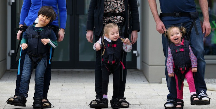 Дети с диагнозом ДЦП ходят со своими родителями при помощи особых костюмов.