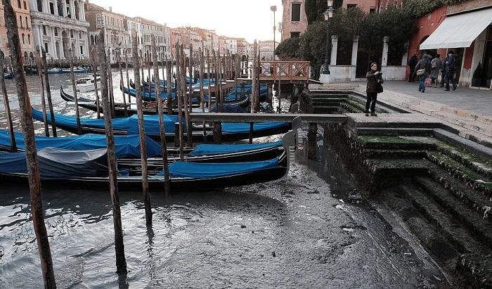 В Венеции гондолы стоят в грязи.