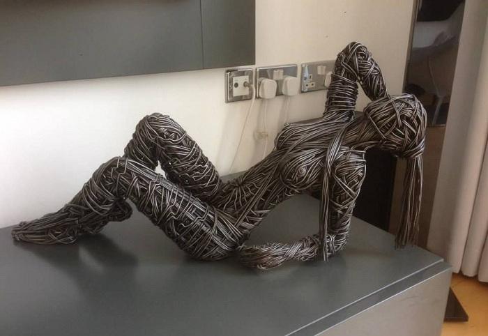 Женский силуэт, выполненный из замотанной проволоки.