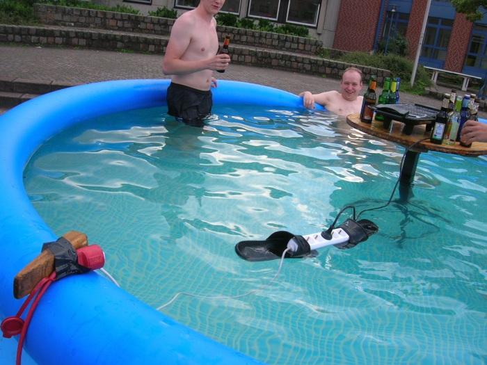 Удлинитель с вставленной в него вилкой, плавает прямо в бассейне.