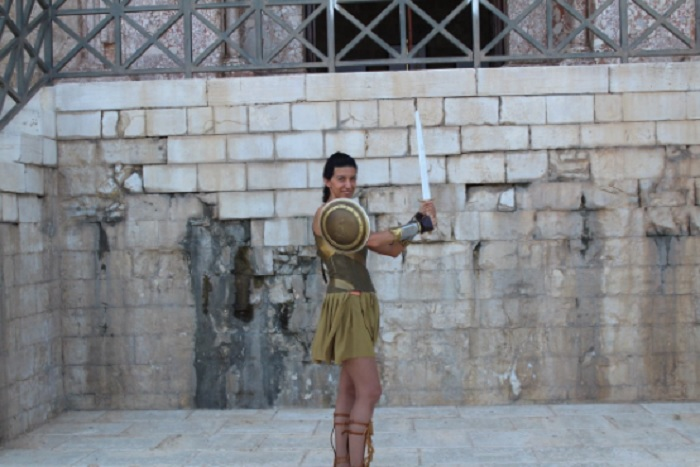 Девушка в костюме амазонке позирует на фоне стен замка Кастель-дель-Монте.   Фото: twitter.com.