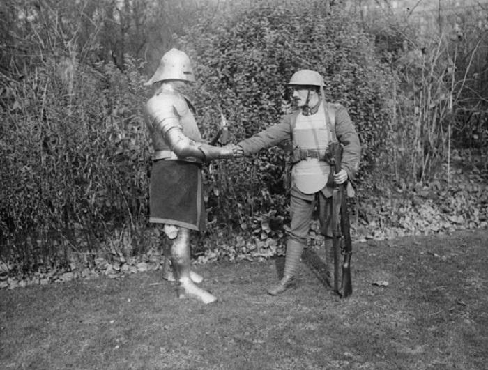 Солдат, вооруженный винтовкой, пожимает руку солдату в доспехах. Октябрь 1917 года. | Фото: vintag.es.