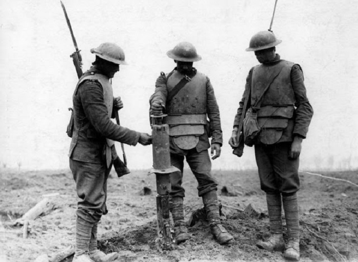 Три ирландский гвардейца, одетые в немецкие бронежилеты, осматривают трофейный немецкий пулемет на хребте Пилкем, 31 июля 1917 года. | Фото: vintag.es.