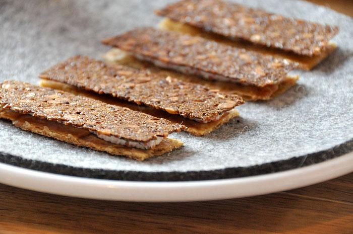 Ржаной хлеб, куриные шкурки с копченым сыром вместе с икрой круглоперовой рыбы.