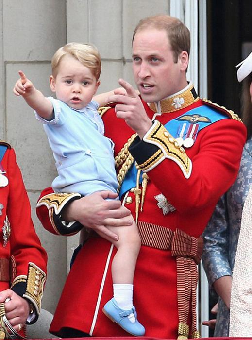 Принц Уильям держит своего сына Джорджа на руках. Они стоят на балконе Букингемского дворца 13 июнь 2015.