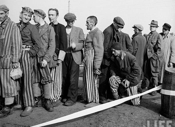 Только что освобожденные заключенные стоят в очереди за едой.