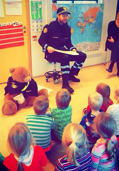 Полицейский плюшевый мишка обучает детишек правилам дорожного движения.