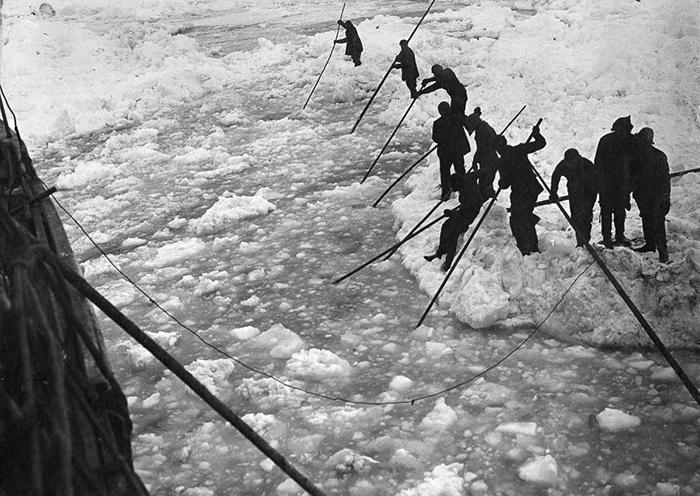 Команда пытается расчистить путь от льда для прохождения судна.