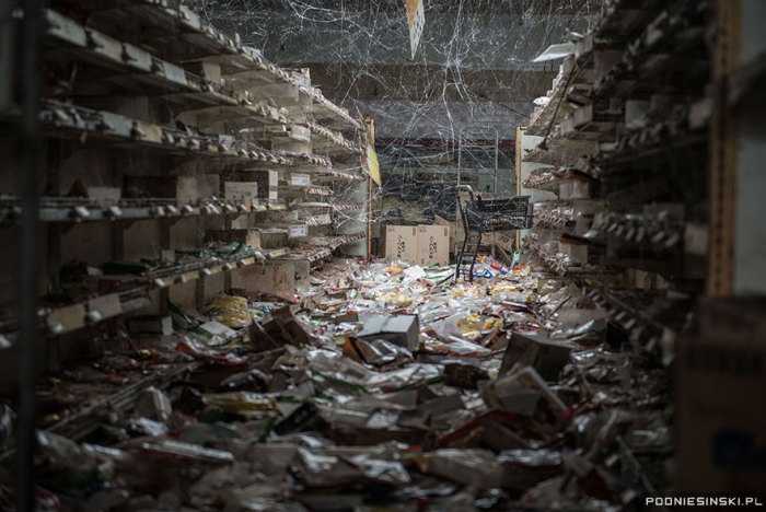 Паутина свисает над товарами в этом покинутом супермаркете.