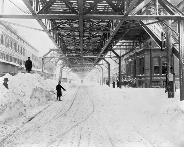 Работники расчищают снег под железной дорогой после метели.