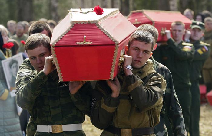 Останки 602 советских солдат, погибших под Ленинградом, теперь покоятся на местном кладбище. Члены поисковой группы собрались у гробов во время погребальной церемонии в Синявино, недалеко от Санкт-Петербурга. 6 мая 2017 г.