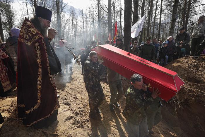 Люди наблюдают, как несут 41 гроб с останками погибших бойцов на место их нового захоронения. Останки 602 бойцов были захоронены в Синявино Ленинградской области.