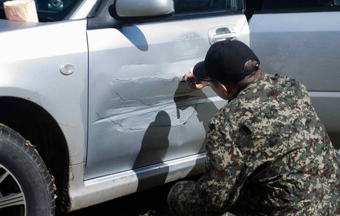 Водитель разрисовывает свой автомобиль.