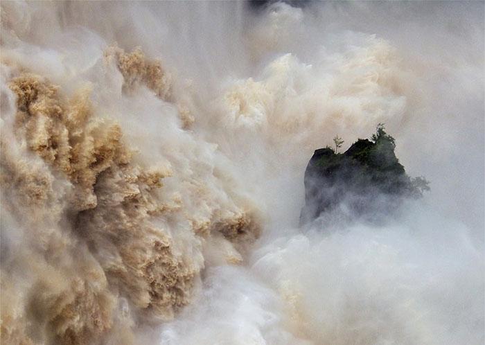 Огромный волны разбиваются оберег вовремя наводнения. Фото: Neil Pritchard.