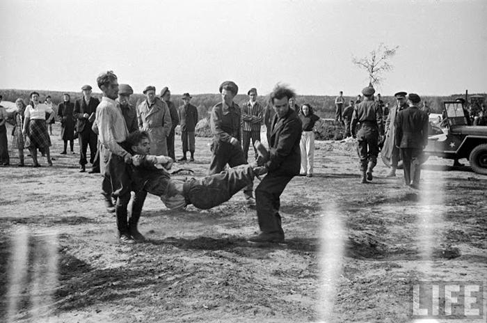 Солдаты СС несут другого солдата, потерявшего сознание от обилия трупов, которых ему пришлось переносить в общую могилу.