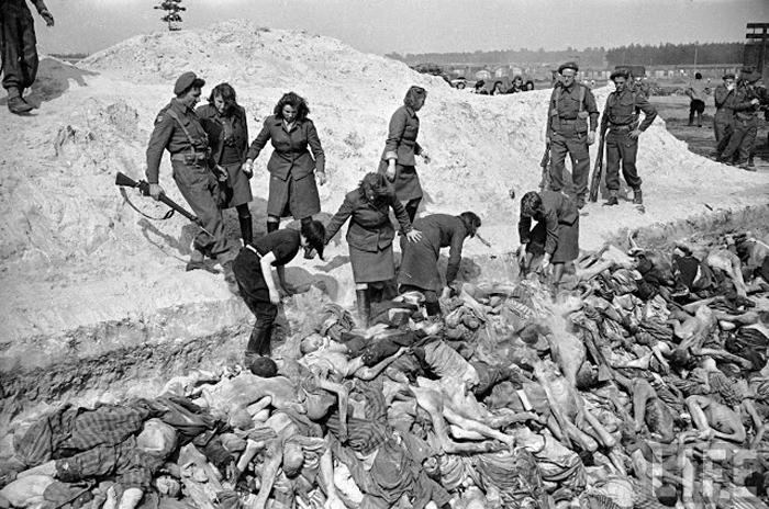 Солдаты-женщины из СС относят умерших заключенных у общую могилу. За ними присматривают солдаты британской дивизии.