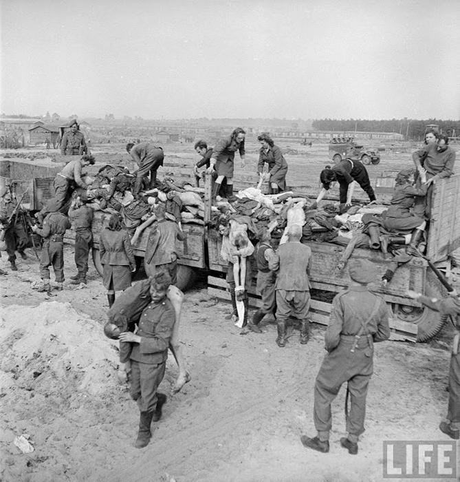 Бывших охранников концлагеря, мужчин и женщин, британские солдаты заставляли переносить мертвых заключенных.
