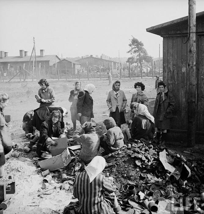 Женщины-заключенные сидят на груде мусора в ожидании еды.
