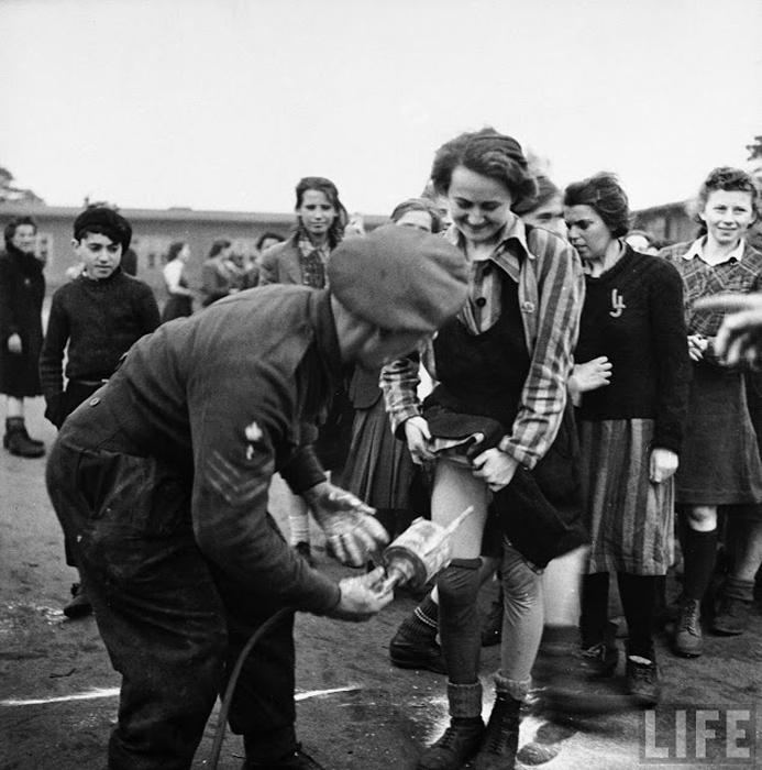 Британский доктор обрабатывает с помощью ДДТ женщин, освобожденных и концлагеря.