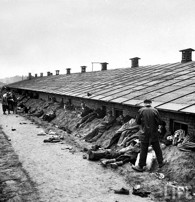 Слабые и умирающие заключенные лежат на насыпи позади бараков концлагеря после его освобождения.