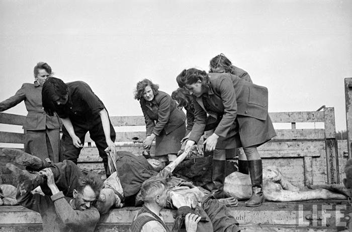 Женский состав охраны концлагеря заставляют разгружать грузовики, заполненные телами.