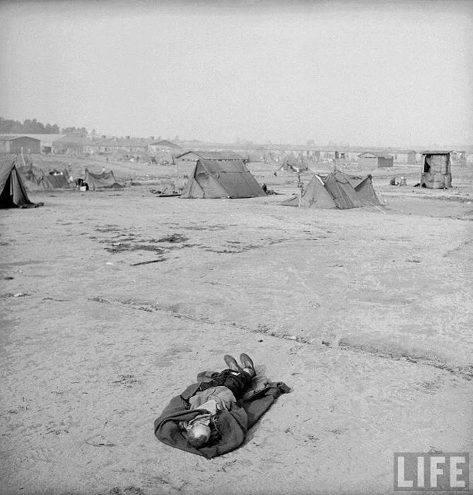 Тело, лежащее на земле в только что освобожденном лагере Берген-Бельзен.