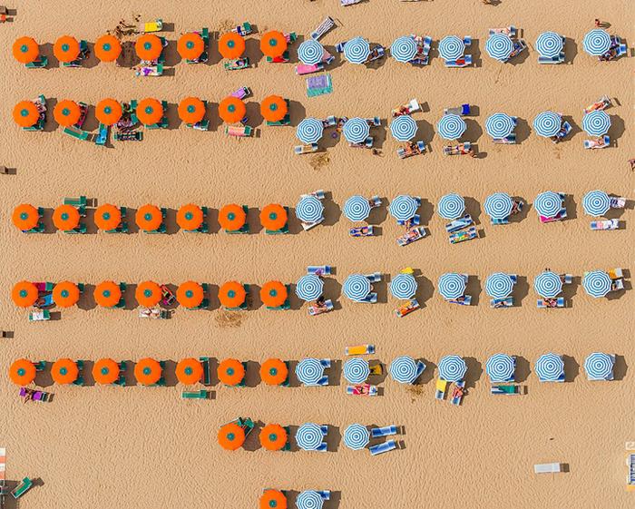 Четкие тени и пляжные зонтики образуют своеобразный паттерн.