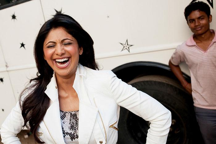 Шилпа Шетти смеется во время съемок рекламы на Mehboob Studio. *В этой жизни слишком много реальности, и потому люди хотят другой мир, жить по-другому. Вот поэтому им и нравится индийский кинематограф.*