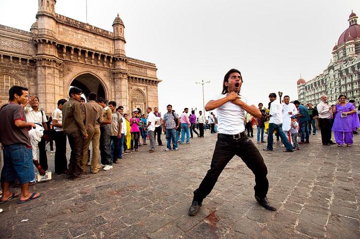 Уличный актер исполняет сцену из классического фильма 1984года *Месть и закон* на улице в Мумбаи.