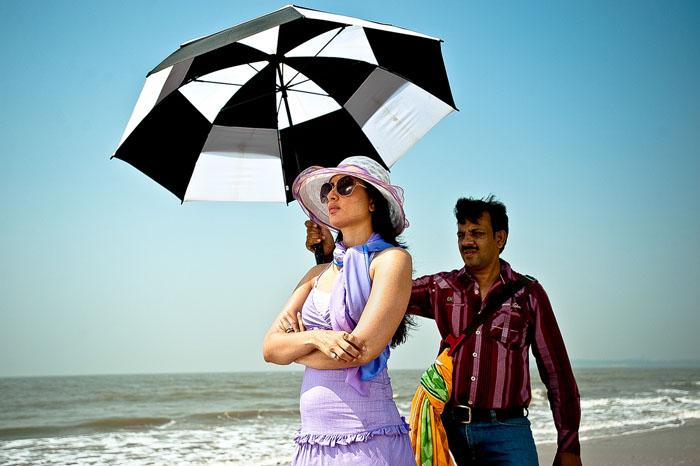 Мужчина держит зонтик над Кариной Капур во время съемок на пляже. *Обо мне ходит много слухов, но я не обращаю на них внимания. Мне кажется, тут это по-другому происходит, чем в Голливуде.*