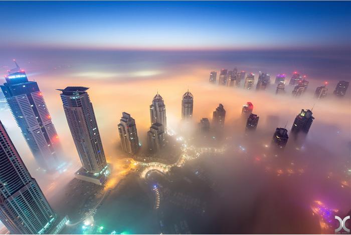 Ночные огни города виднеются сквозь густой туман.