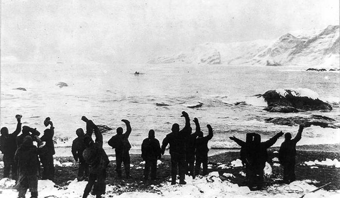 Члены экипажа машут шлюпке Шеклтона, на которой шесть человек отправились к острову Южная Георгия.