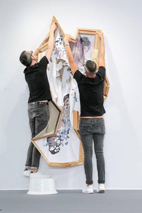 Дизайнеры снимают полотна со стены.