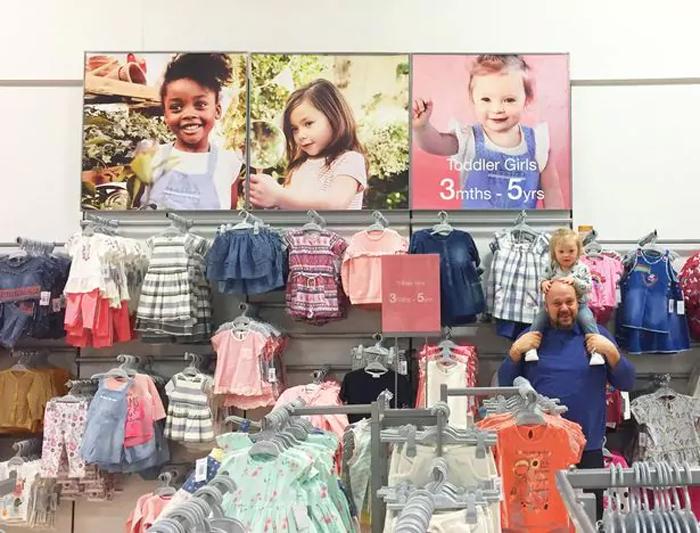Папа Эдди со своей дочерью Лили на фоне рекламного плаката с ее портретом.