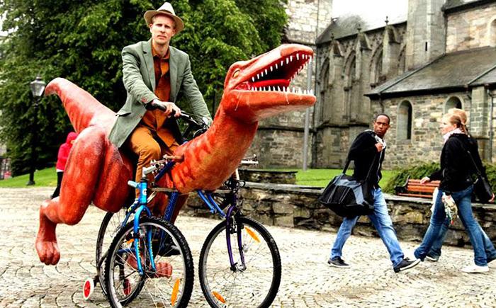 Норвежский художник протестует с помощью динозавра на велосипеде.