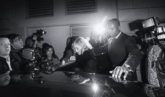 Телохранитель помогает Мадонне пробраться к ожидающему ее автомобилю. Фото: Max Butterworth.