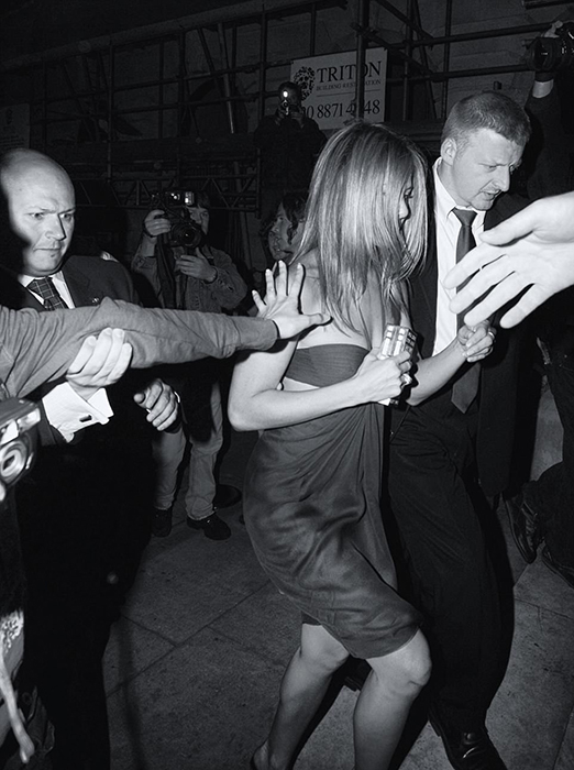 Звезда телесериала *Друзья* Дженнифер Энистон старается быстрее пройти мимо папарацци после вечеринки в Лондоне. Фото: Max Butterworth.