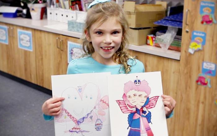 Школьница держит свой рисунок и версию художника.