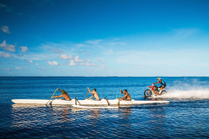 Проезжая на мотоцикле мимо плывущей лодки.